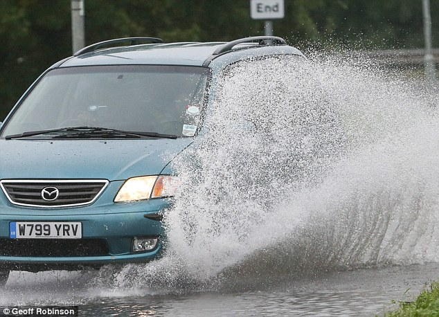 Making it through: Cars driving along a flooded road in Huntingdon, Cambridgeshire, yesterday