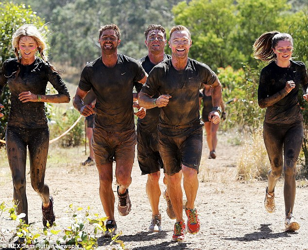 Nearly there: Ronan Keating and girlfriend Storm Uechtritz along with some other fitness fanatics run together as they almost finish the gruelling course