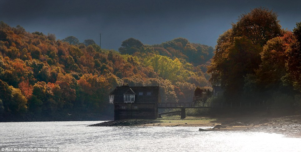 Autumn scene: The sun briefly shines through storm clouds illuminating leaves surrounding a house known as the Lady of The Lake at Rudyard Lake, Staffordshire