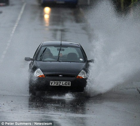 Cars having to negotiate large puddles in Birmingham this morning