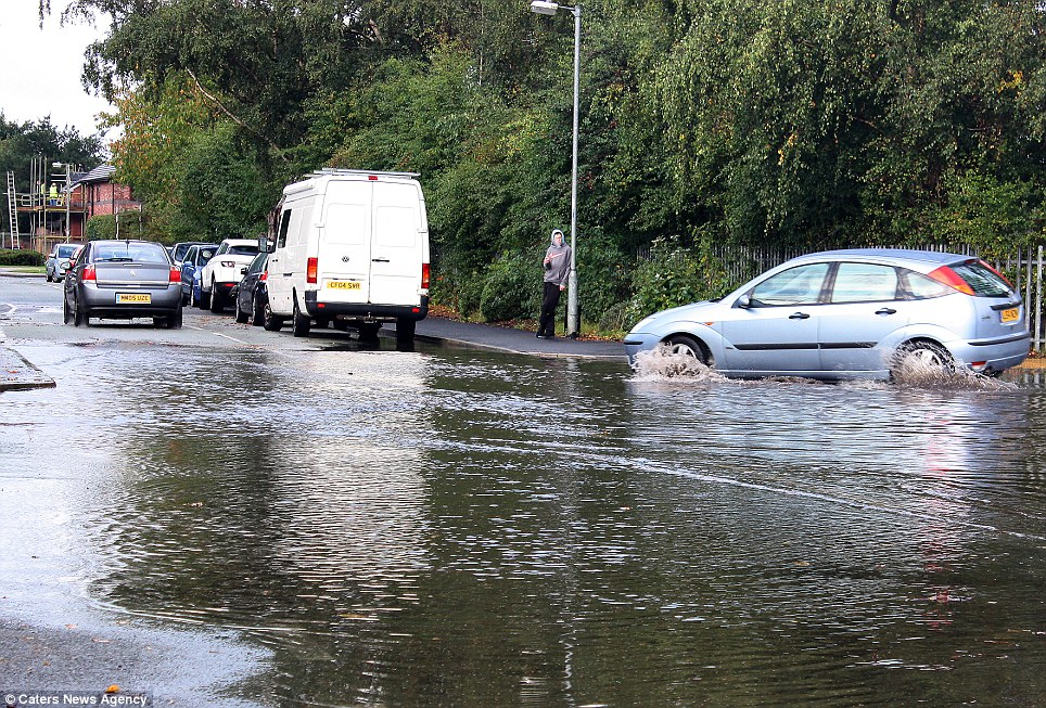 Wet weather: Flooding in Wrexham, North Wales, was pictured today as motorists tried their best to make their way around the area