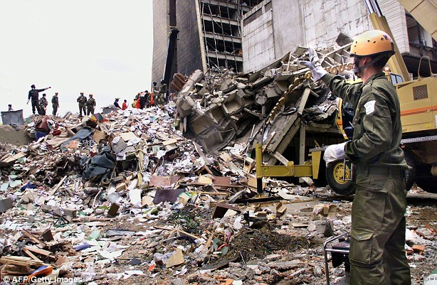 Reduced to rubble: An Israeli rescue worker (R) calls to colleagues as they stand on what remains of a building in front of the US embassy in Nairobi