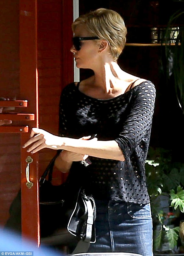 Roles reversed: Charlize held open the door for her companion, as she showed off her natural beauty with minimal makeup and her cropped haircut
