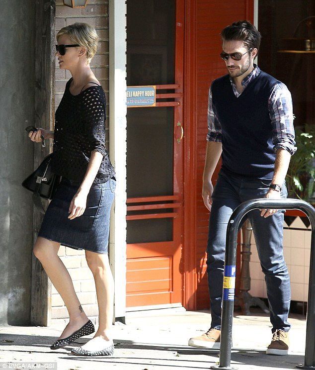 Casual style: The South African beauty showed off her toned legs in denim skirt as she made her way into the restaurant with the handsome gentleman