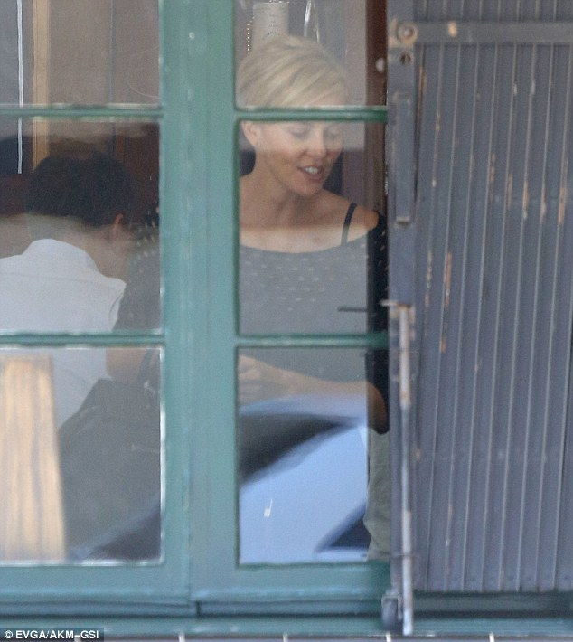 In her element: Charlize looked to have a good rapport with her lunch companion as she chatted with him while getting up from her table