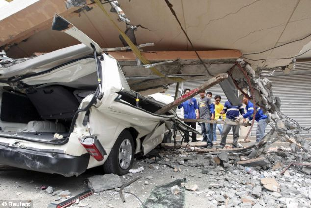 Destruction: Residents inspect a car after a concrete block fell on it during an earthquake in Cebu city
