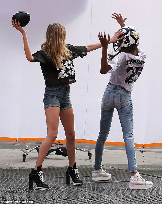 Team work: Models Cara Delevingne and Jordan Dunn were spotted on the set of a DKNY photo shoot in New York City, New York getting stuck in to a fake game of American football