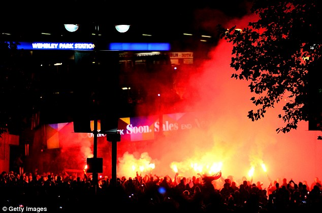 Red mist: Smoke fills the air around Wembley Park underground station as Poland fans light flares