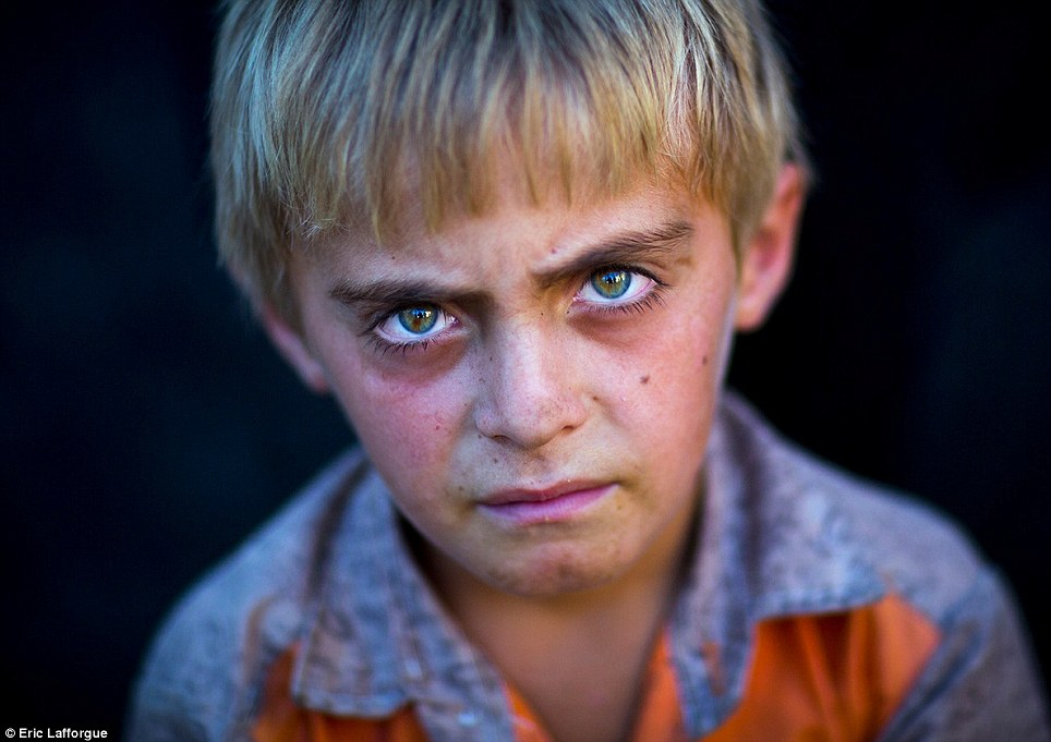 Haunted: This young boy's face bears traces of his recent ordeal. His blond hair and green eyes are thought to be the result of Russian ancestors who married Kurdish women