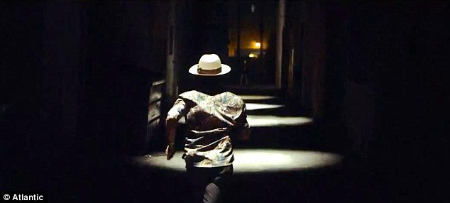Watch you back: Bruno is then seen running down a dimly lit corridor as a real gorilla grunts and runs after him