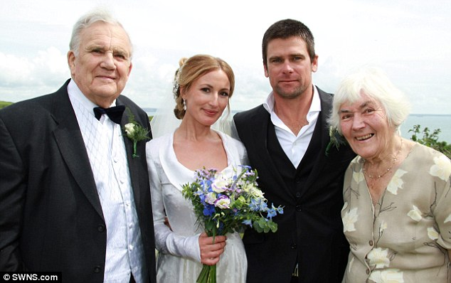 Romantic: Lucy wearing the vintage dress on her wedding day, flanked by her husband Mark and her grandparents