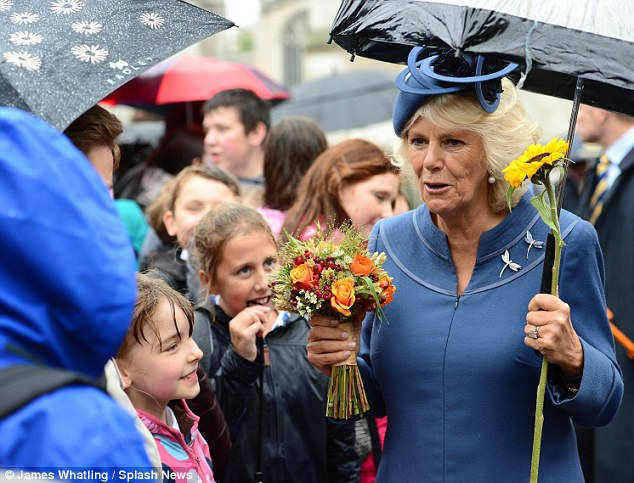 Radiant: Camilla appeared to be in good spirits as she mingled with the crowds on a rainy day in central London