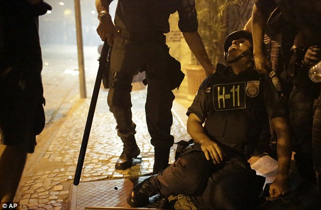 Struggling to breathe: A police officer is overcome with tear gas inhalation