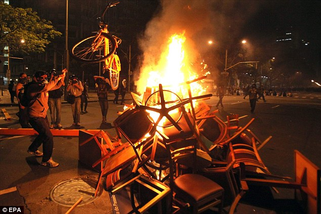 Burning issue: Protestors set tables, chairs and even bikes alight as they marched for education reform in Rio