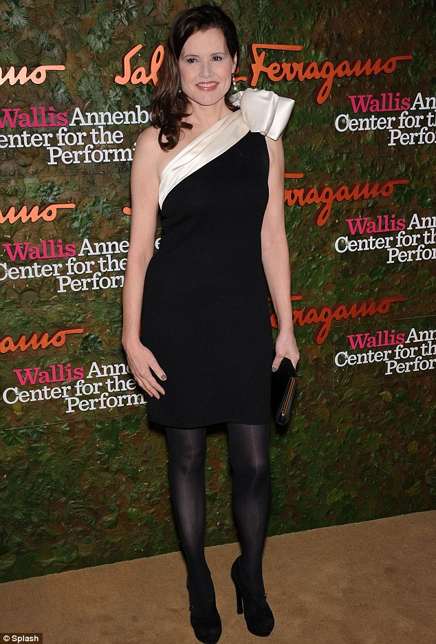 Black and white delight: Geena Davis wore a one shouldered black dress with white trim teamed with practical black tights and high heeled black boots