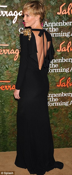 Golden girl: Charlize Theron looked the picture of elegance in a slinky black dress with gold shoulder details