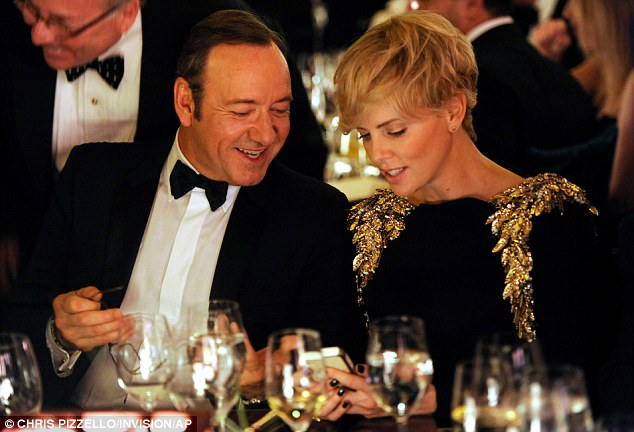 Dinner buddies: Perhaps Chralize was showing Kevin Spacey snapshots of her son Jackson