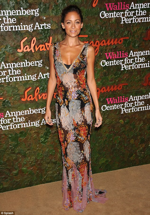 Grin and bare it: Fashionista Nicole Richie turned up at a Beverly Hills gala in a revealing dress and barely there make up that made the most of her golden tan