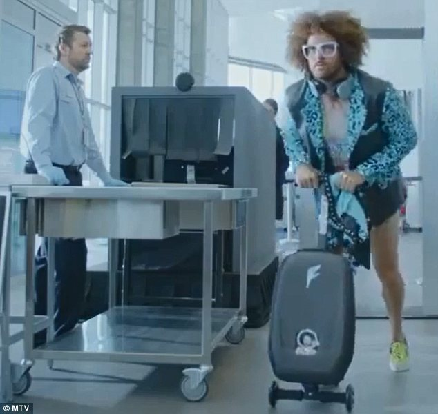 Off we go: Redfoo could be seen whizzing off while riding on a wheelie suitcase at the end of the advert