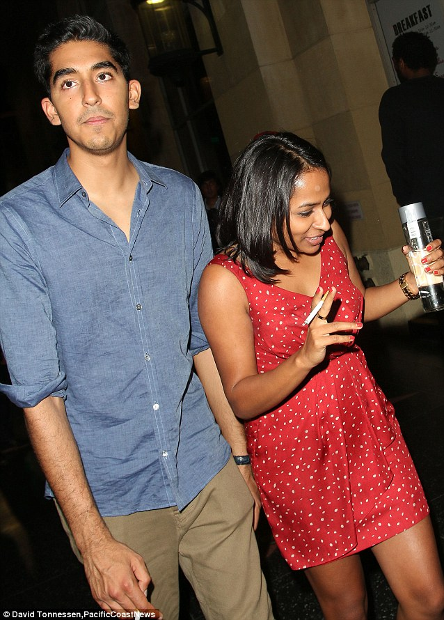 Partners in ciggies: Dev Patel and a female friend both enjoy a cigarette as they leave the Roosevelt hotel after celebrating Freida Pinto's birthday
