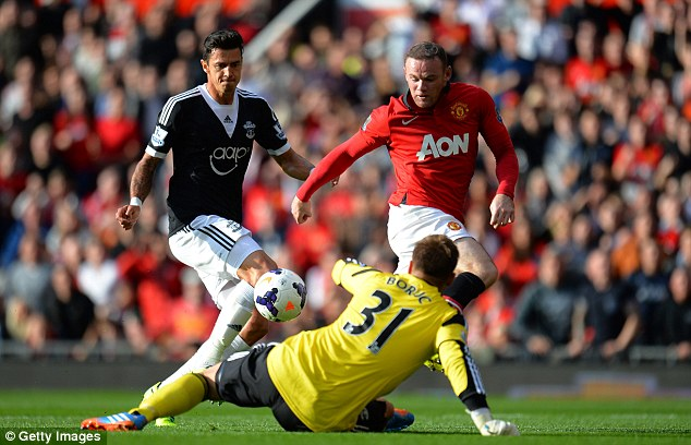 In action: Wayne Rooney (right) tries to lift the ball over Artur Boruc during United's clash with Southampton