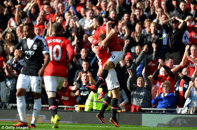 Delight: Van Persie jumps into the arms of Michael Carrick in celebration at giving United the lead