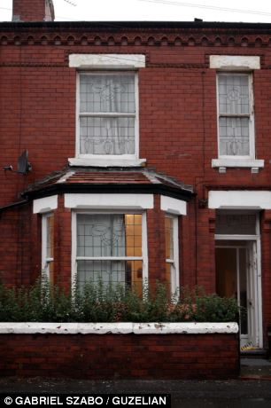 The wrong house: The mid-terrace home (left) was wrongly gutted by workers