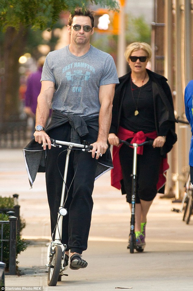 Catch me if you can: Hugh speeds ahead of his wife with his bulging muscles on show