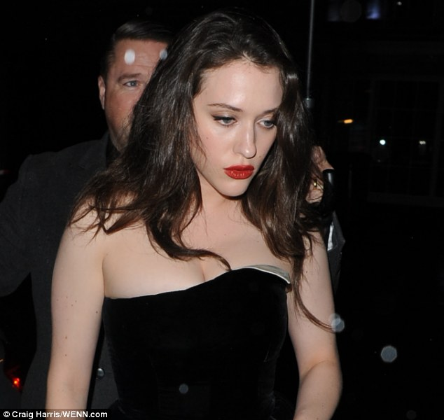 British weather: Kat Denning's hid under an umbrella to escape the London drizzle as she arrived at Sake No Hana  for the after show party