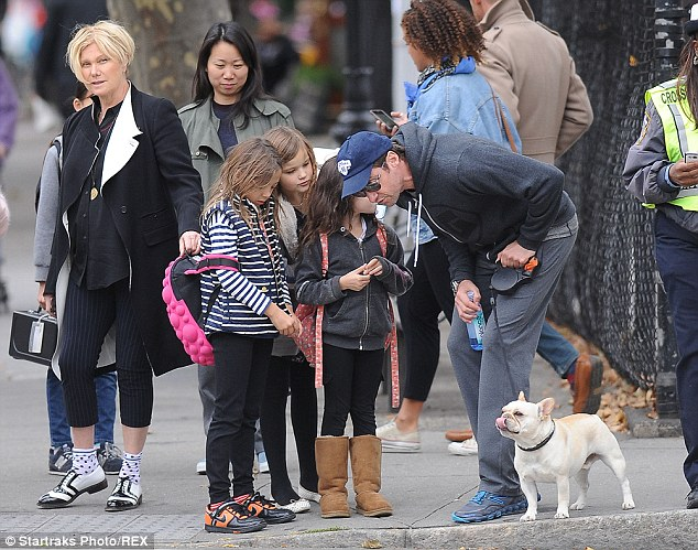 A dogs life: Hugh Jackman and Ava fuss over the family pooch Dali while his wife Deborra-Lee Furness protectively holds on to her daughter's bag as they wait to cross the road