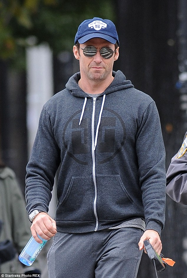 Tight leash: Hughes attempts to go unnoticed in mirrored sunglasses and a baseball cap failed, but the actor didn't seem to mind