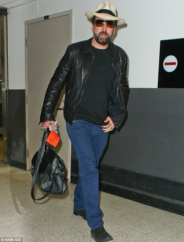 Back home: Nic Cage arrived at Los Angeles International Airport from China on Wednesday after wrapping filming on US-China co-production Outcast. The star wants Hollywood to use more Asian actors in films.