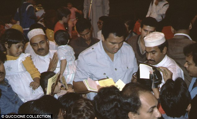 Crowds: In another unseen photo, Muhammed Ali is surrounded by fans on a visit to the Middle East