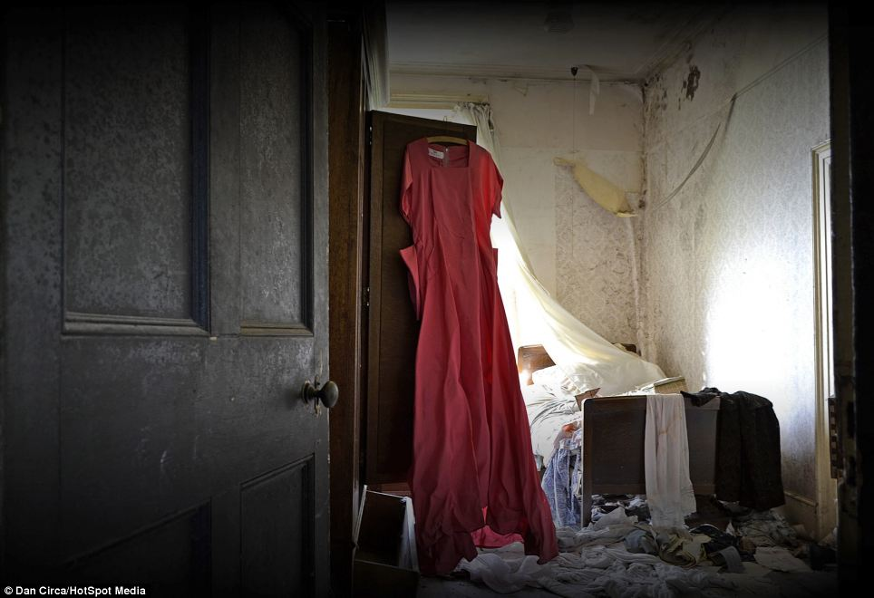 Crumpled and beautiful: The red dress pictured in a photo on the wall was found hanging in an empty wardrobe, while other clothes clutter the floor