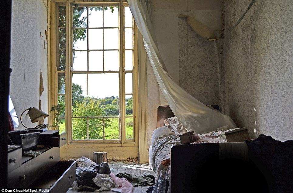 Battered: The window panes are broken, the curtain is pulled across the room, and there are clothes scattered