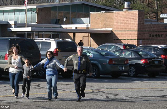 Terror: The massacre by 20-year-old gunman Adam Lanza, a former Sandy Hook student, was one of the worst school shootings in U.S. history. A police officer leads two women and a child during the attack
