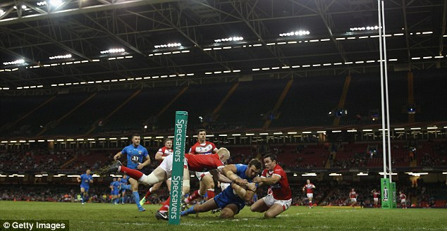 Going over: Joshua Mantellato of Italy scores a try despite the efforts of Rhys Evans and Matt Seamark
