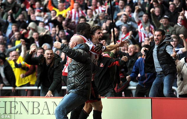 Delirium: After his magnificent winner, Borini celebrates wildly with Jozy Altidore and ecstatic Sunderland fans