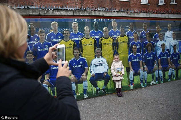 New member of the team: Chelsea fan Katie Anthony, 7, poses with a mural of the squad outside Stamford Bridge
