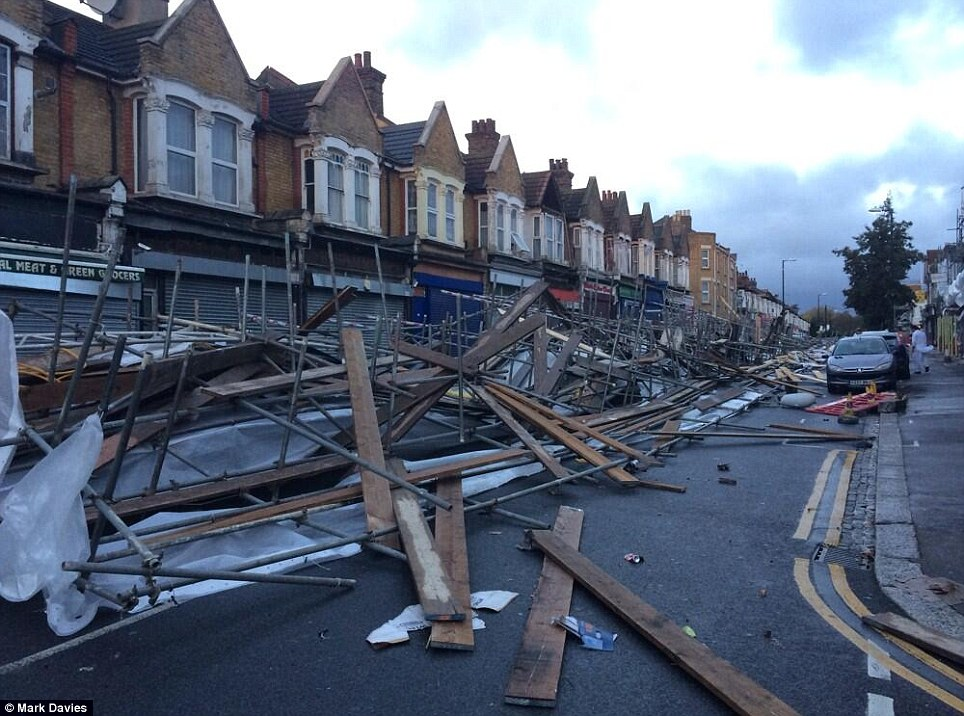 Carnage: This street in Leyton, east London was strewn with debris after raging winds tore down shopfront scaffolding