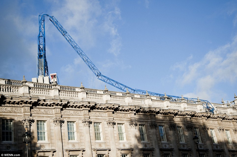 Broken: The hurricane-force winds snapped this crane held high above Downing Street, which has collapsed onto the roof of the Cabinet Office