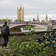 A fallen branch is seen as a man walks towards Lambeth Bridge