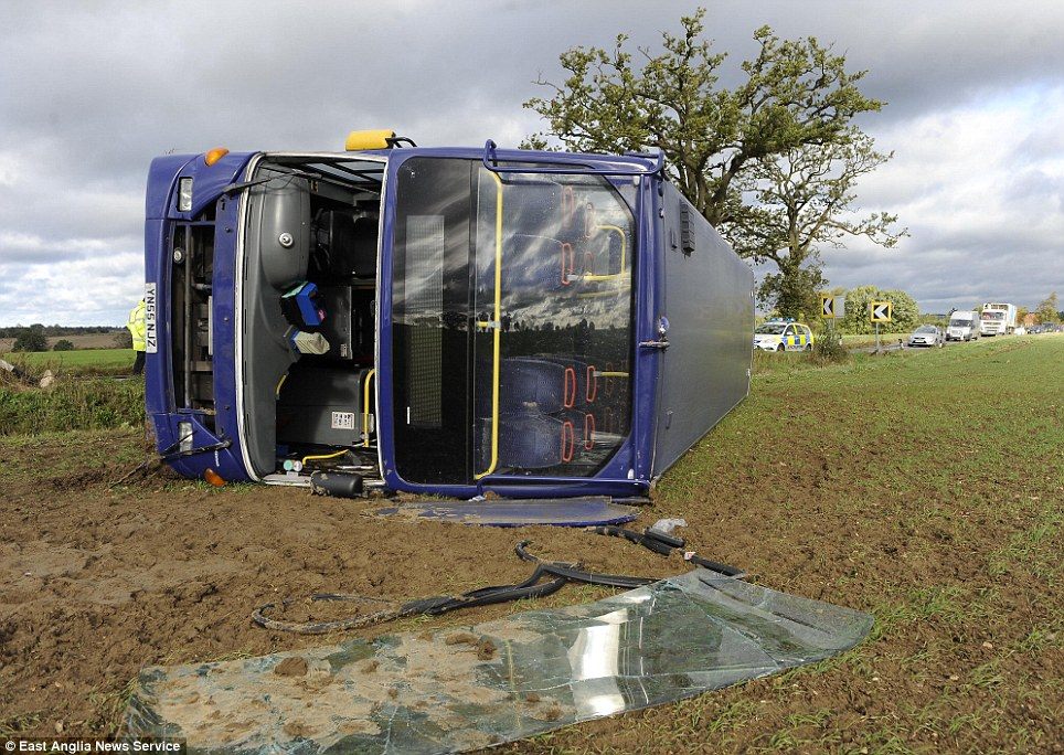 The front window of the bus lies shattered on the ground after the accident, on the A1071 near Hadleigh in Suffolk. It is believed that while passengers escaped serious injury - the driver has been taken to hospital