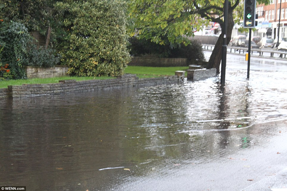 Difficult conditions: Flooding could be seen on the North Circular road in Highgate, north London, making it tough for cars to make their way through