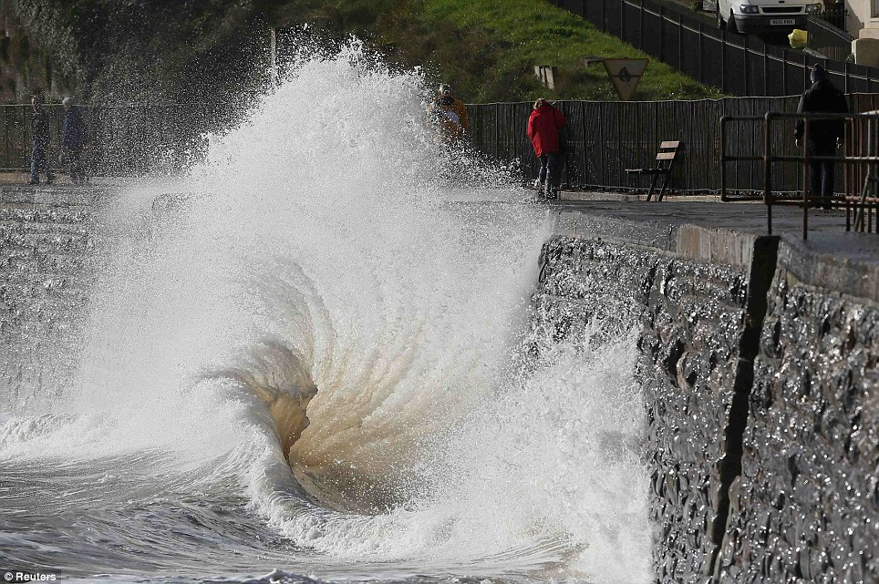 Swirl: People walk as waves crash against the seafront at Dawlish in Devon. Britain's strongest storm in a decade forced hundreds of flight cancellations