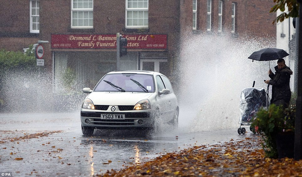 Splash: A lady with a child in a pram gets an unwelcome soaking from a passing car in the Gateacre area of Liverpool, after heavy rain fell over the country