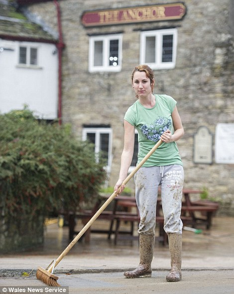 Helena Woodford cleaning the outside of The Anchor pub in Tintern, South Wales, which flooded during heavy rain and storms overnight