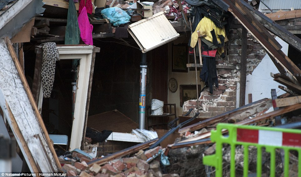 Torn apart: An explosion involving three houses in Hounslow, west London. The wreckage of the front of the houses that were hit is pictured
