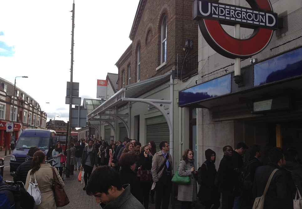 Scores of commuters queue out of Balham station, in south west London. At least 15 different train companies have cancelled services
