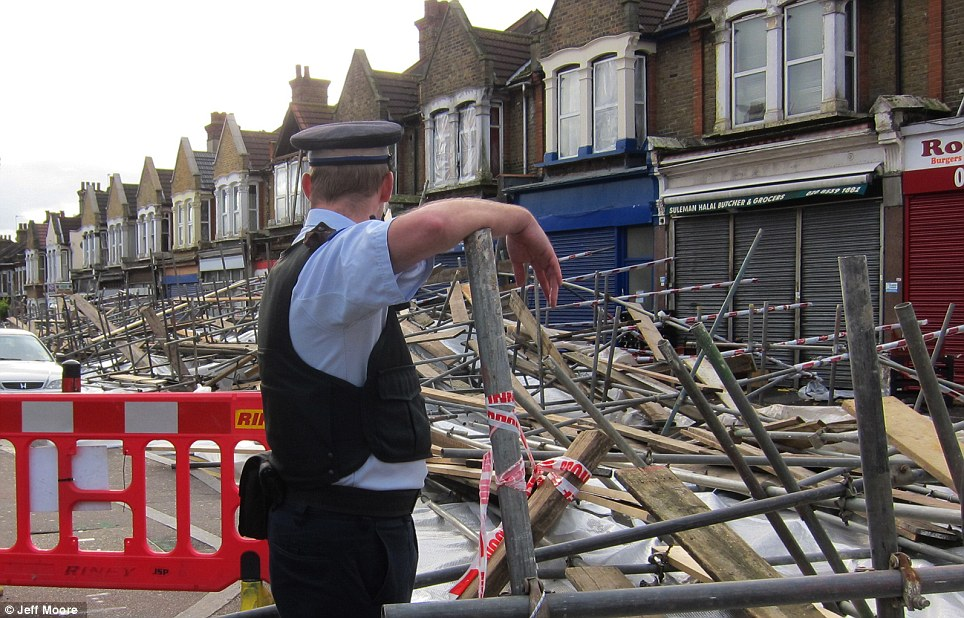 A police officer surveys the scene after scaffolding collapsed on top of cars in a street in Leyton, East London yesterday morning